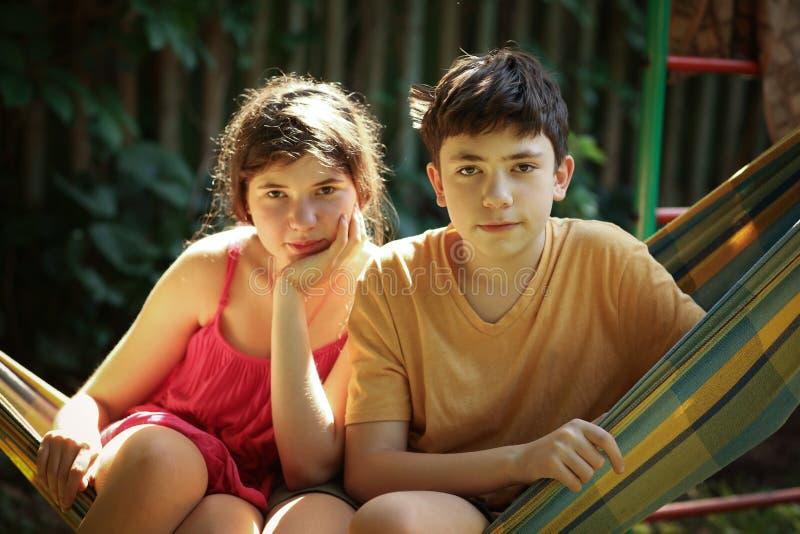 Tonåringsyskon pojke och flickasyskongruppslut upp det utomhus- fotoet för sommar royaltyfri bild