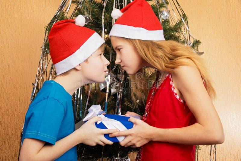 Tonåringsyskon som försöker jokingly att snappa sig julgåva för ` s royaltyfri bild