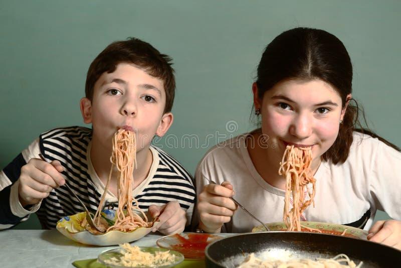 Tonåringsyskonsyskongrupp som äter spagetti arkivbilder