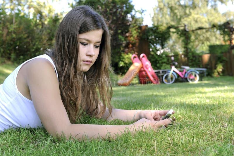 tonårs- älskvärd telefon för cellflicka royaltyfria foton