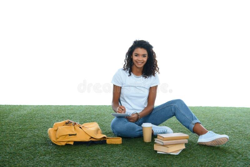 tonårs- afrikansk amerikanstudentflicka som studerar, medan sitta på gräs arkivbild