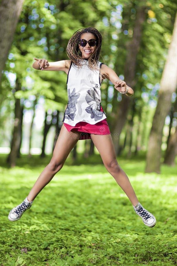 Tonårs- flicka för aktiv och lycklig afrikansk amerikan med Dreadlocks som gör en höjdhopp royaltyfria foton