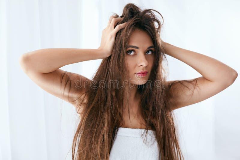 Tonårs- flicka för blond kvinna som visar henne skadat torrt hår Kvinna med torrt och skadat långt hår royaltyfri foto