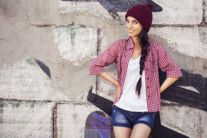 Tonårs- flicka för brunett i hipsterdräkt (jeans kortsluter, keds, plädskjorta, hatt), med en skateboard på parkera royaltyfri bild