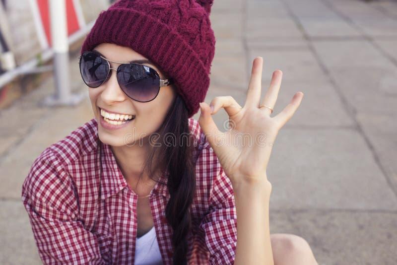 Tonårs- flicka för brunett i hipsterdräkt (jeans kortsluter, keds, plädskjorta, hatt), med en skateboard på parkera fotografering för bildbyråer