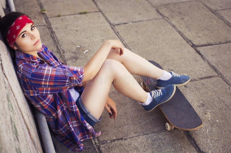 Tonårs- flicka för brunett i hipsterdräkt (jeans kortsluter, keds, plädskjorta, hatt), med en skateboard på parkera utomhus royaltyfria foton