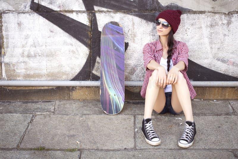 Tonårs- flicka för brunett i kortslutningar för hipsterdräktjeans, keds, plommoner royaltyfri fotografi