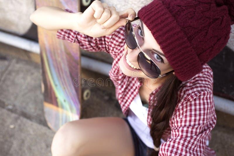 Tonårs- flicka för brunett i kortslutningar för hipsterdräktjeans, keds, plommoner royaltyfri bild