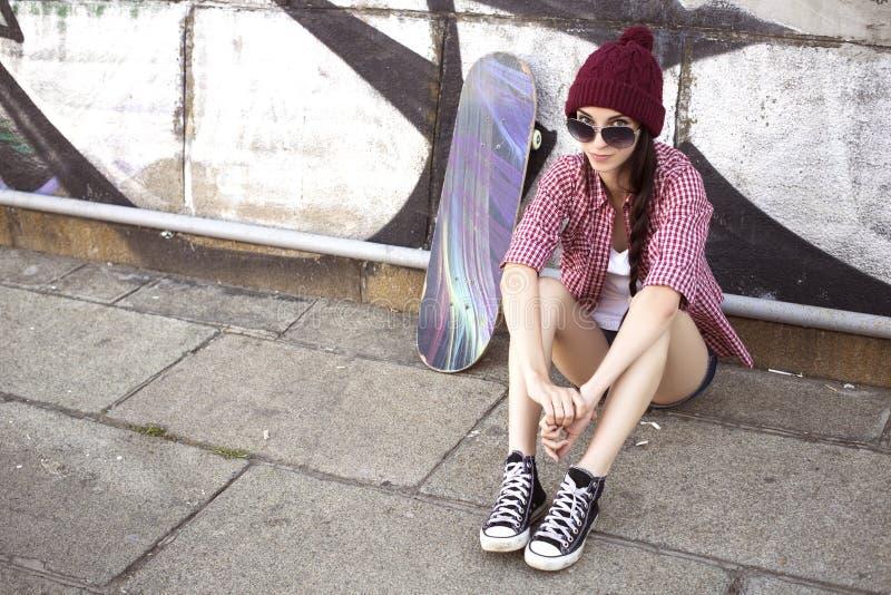 Tonårs- flicka för brunett i kortslutningar för hipsterdräktjeans, keds, plommoner arkivbild
