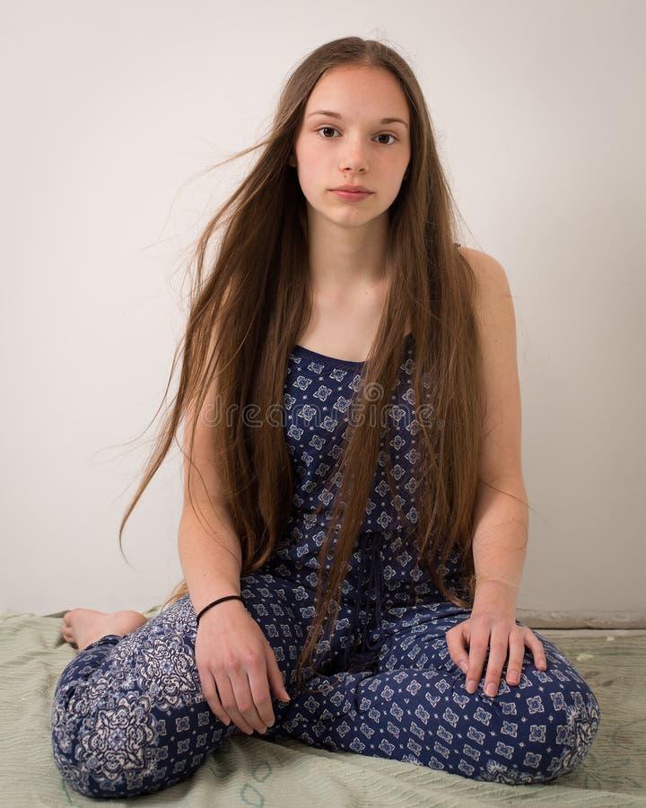 Tonårs- flicka för härlig brunett i blå pyjamas fotografering för bildbyråer