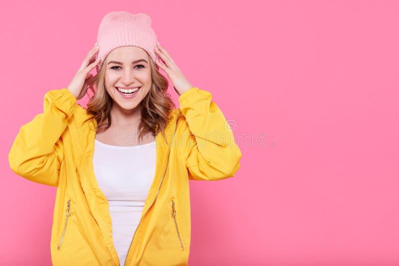 Tonårs- flicka för härlig hipster i upphetsat för hatt för ljust gult omslag och rosa färgbeanietoppet Attraktiv kall stående för royaltyfria bilder