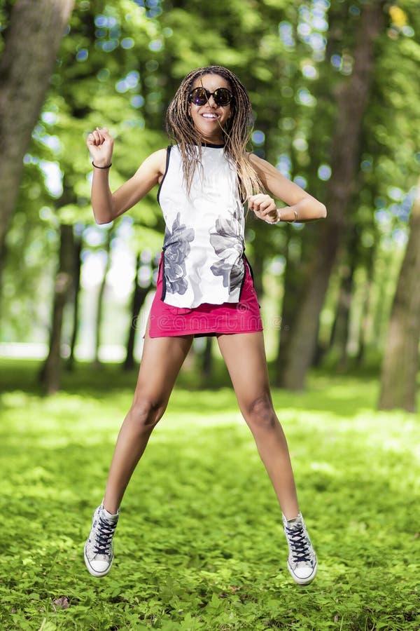 Tonårs- flicka för lycklig afrikansk amerikan med Dreadlocks som gör en höjdhopp arkivbilder