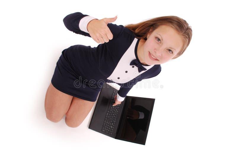 Tonårs- flicka för lycklig student med bärbara datorn Sitta från sidan och rymma upp tummen fotografering för bildbyråer