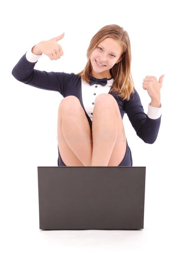 Tonårs- flicka för lycklig student med den hållande tummen för bärbar dator upp arkivfoto