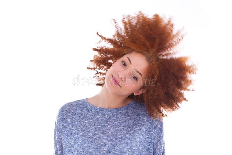 Tonårs- flicka för ung afrikansk amerikan som spelar med hennes lockiga hår arkivfoto