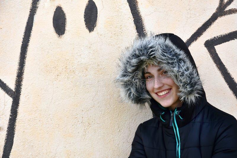 Tonårs- flicka framme av en grafittivägg arkivbilder