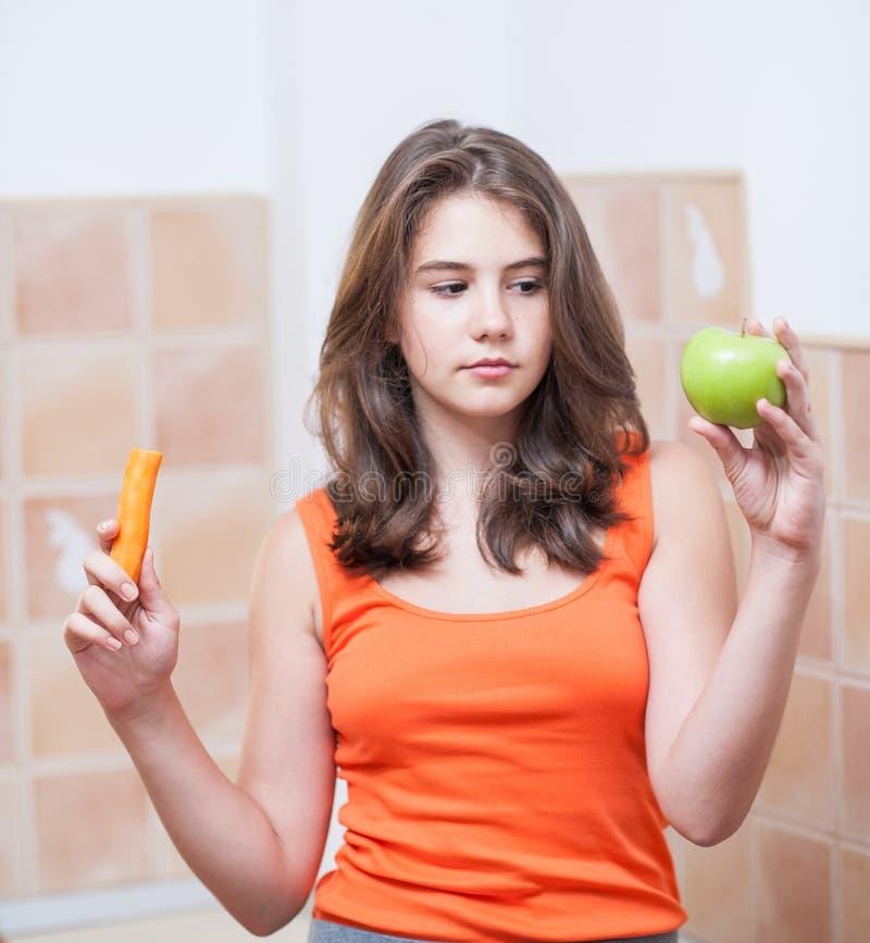 Tonårs- flicka i den orange t-skjortan som har frukter i hennes händer royaltyfria foton