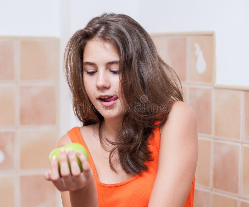 Tonårs- flicka i den orange t-skjortan som ser ett grönt äpple royaltyfri foto