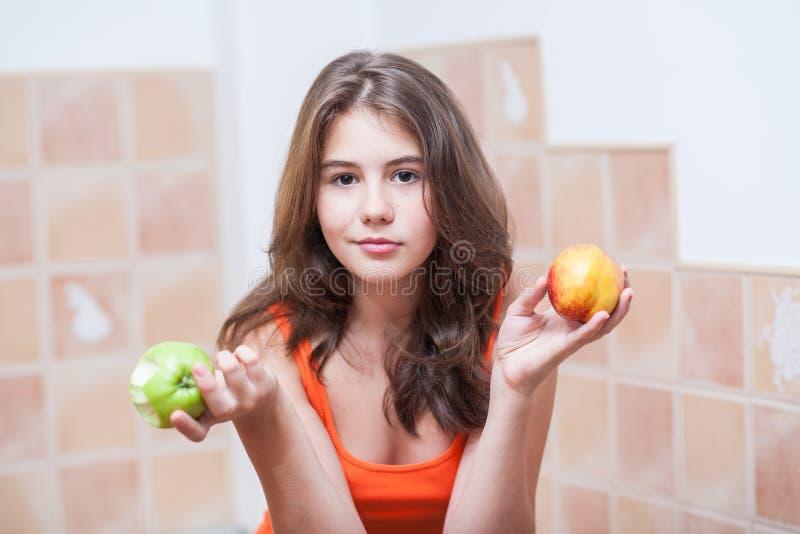 Tonårs- flicka i den orange t-skjortan som ser kameran som har ett grönt äpple och en persika i henne händer royaltyfri fotografi
