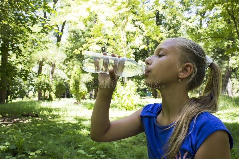 Tonårs- flicka i en parkeradricksvattenflaska med en handholdi arkivbild