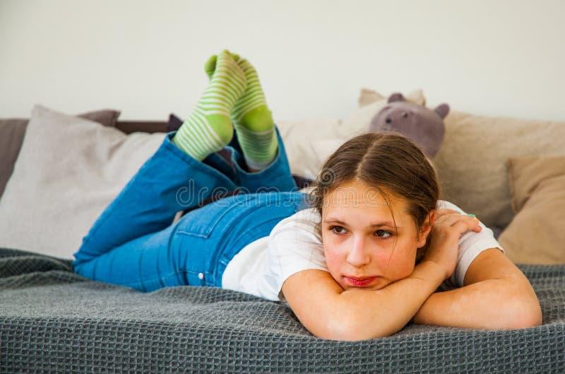 Tonårs- flicka i jeans som lägger i hennes säng royaltyfria foton