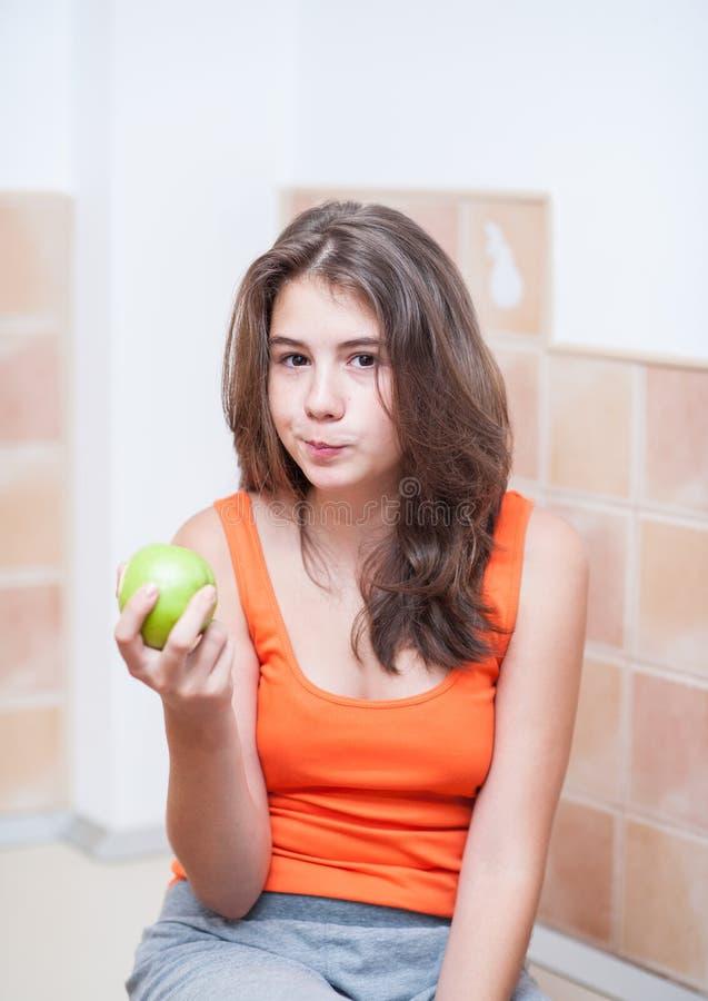 Tonårs- flicka i orange t-skjorta som äter ett grönt äpple royaltyfri bild