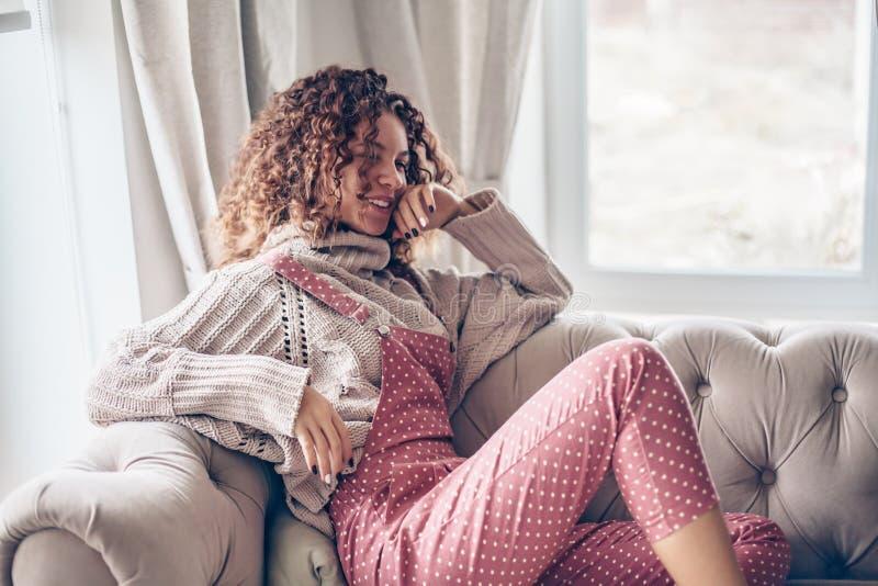 Tonårs- flicka i tröja och jumpsuit på en soffa arkivbild