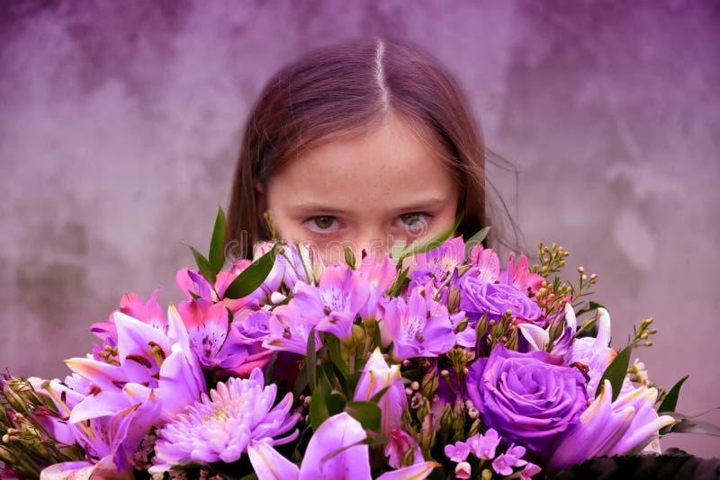 Tonårs- flicka med den stora gruppen av färgrika blommor arkivfoton
