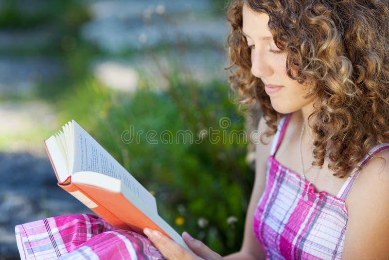 Tonårs- flicka med lockigt hår som läser en bok arkivbild