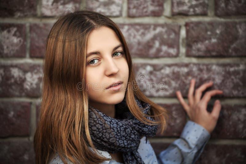 Tonårs- flicka mot en tegelstenvägg arkivfoto