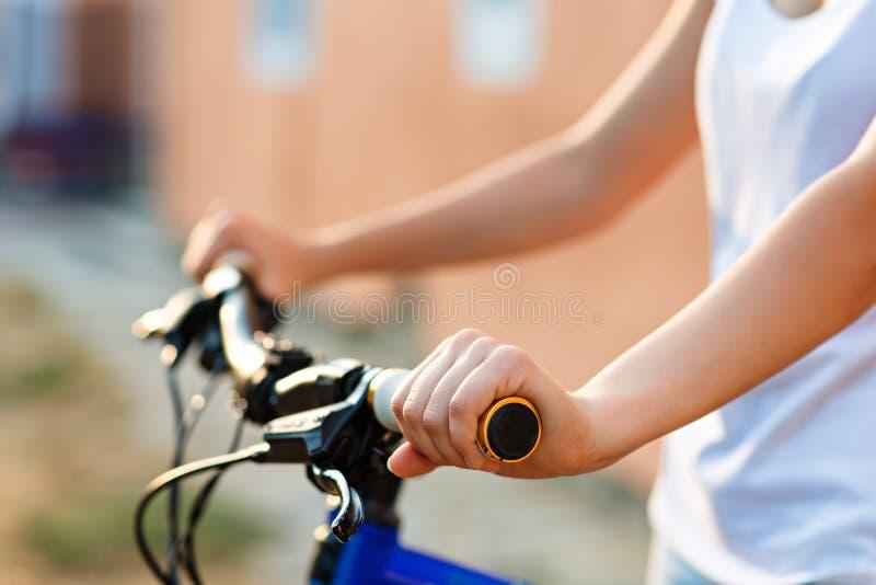 Tonårs- flicka och cykel i stad arkivfoto