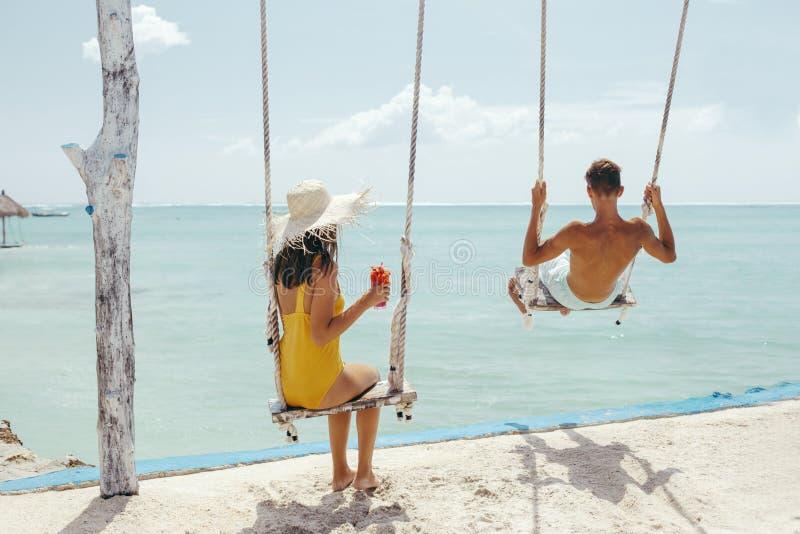 Tonårs- flicka och pojke som hänger på gungor med en havssikt i strandkafé royaltyfri foto