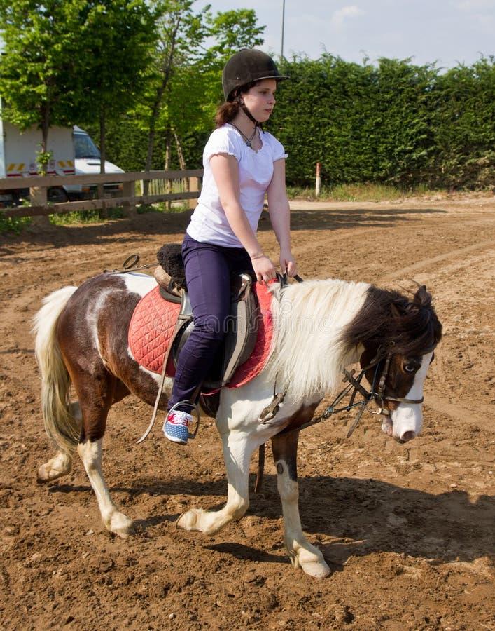 Tonårs- flicka på bärande hjälm för hästrygg arkivbild