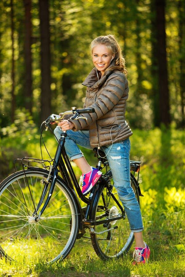 Tonårs- flicka på en cykel utomhus royaltyfri fotografi