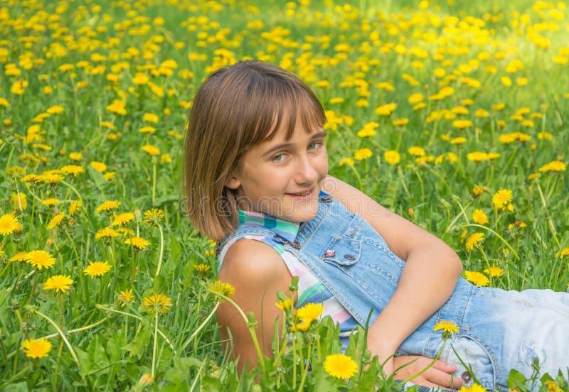 Tonårs- flicka på gräsmatta med gula maskrosor fotografering för bildbyråer