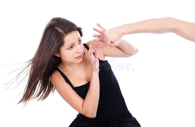 Tonårs- flicka som är rädd av en hand som slår henne royaltyfri foto
