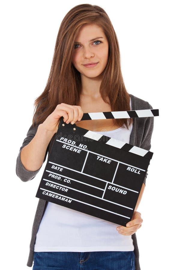 Tonårs- flicka som använder clapperboard royaltyfri foto