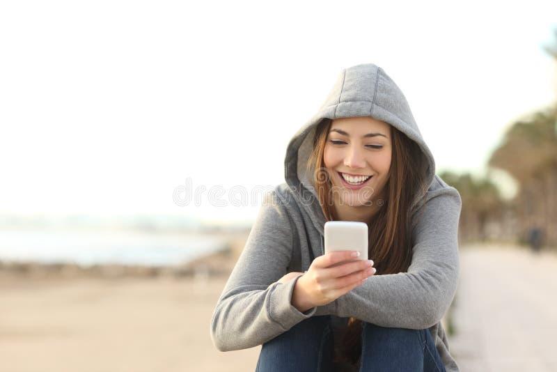 Tonårs- flicka som använder en smart telefon på stranden arkivfoto