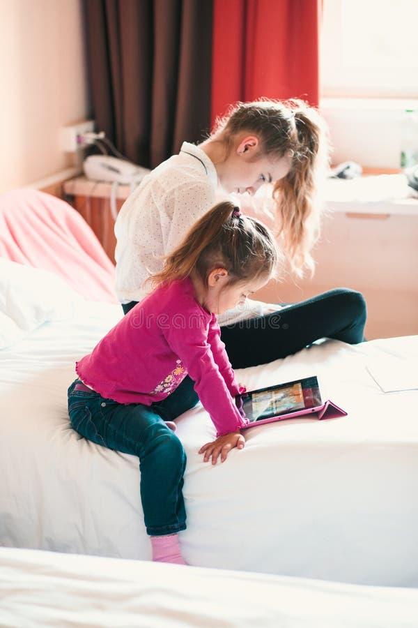 Tonårs- flicka som använder mobiltelefonen samman med hennes lilla syster som håller ögonen på livlig film på minnestavlan arkivfoto