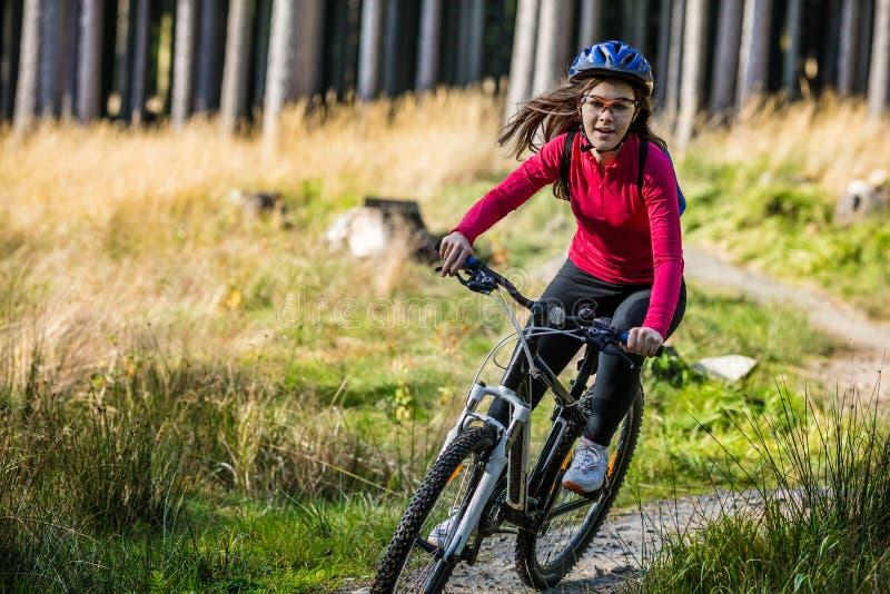 Tonårs- flicka som cyklar på skogslingor royaltyfria foton