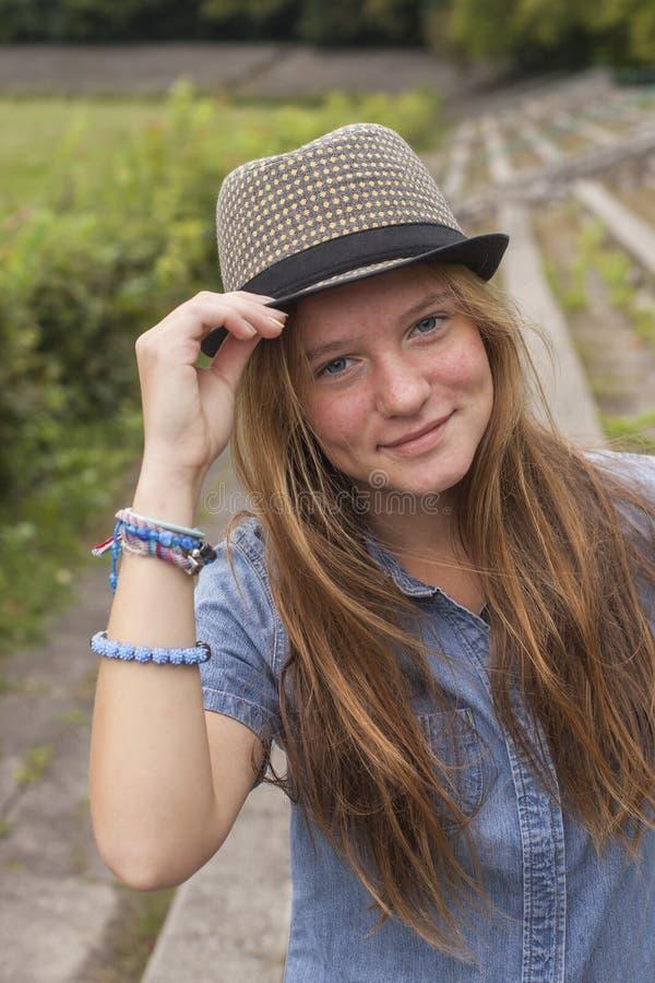Tonårs- flicka som framme poserar i en parkera av kameran gå arkivfoto