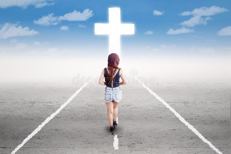 Tonårs- flicka som går till korset arkivbilder