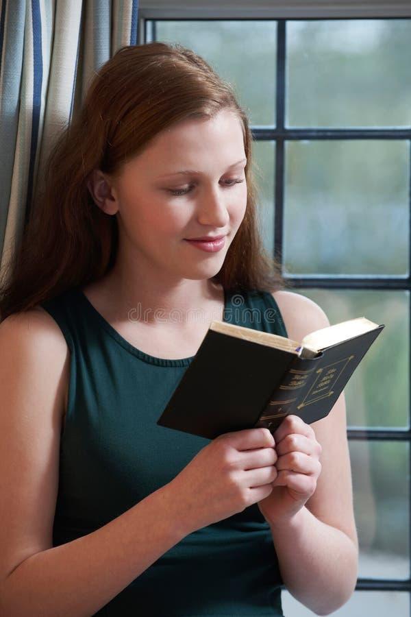 Tonårs- flicka som hemma läser hennes bibel arkivfoton