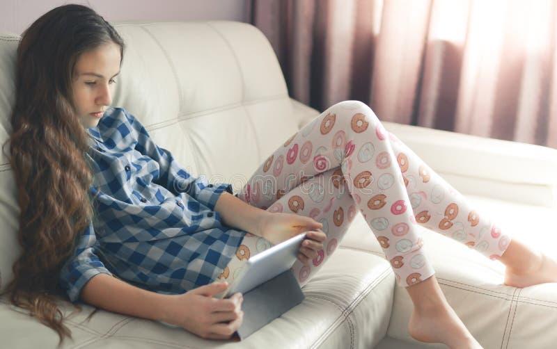 Tonårs- flicka som hemma sitter med en minnestavlaPC Livsstilbild av den härliga Caucasian långhåriga flickan arkivbilder