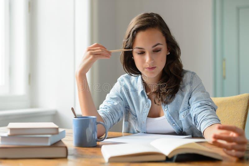Tonårs- flicka som hemma studerar läseboken royaltyfria foton