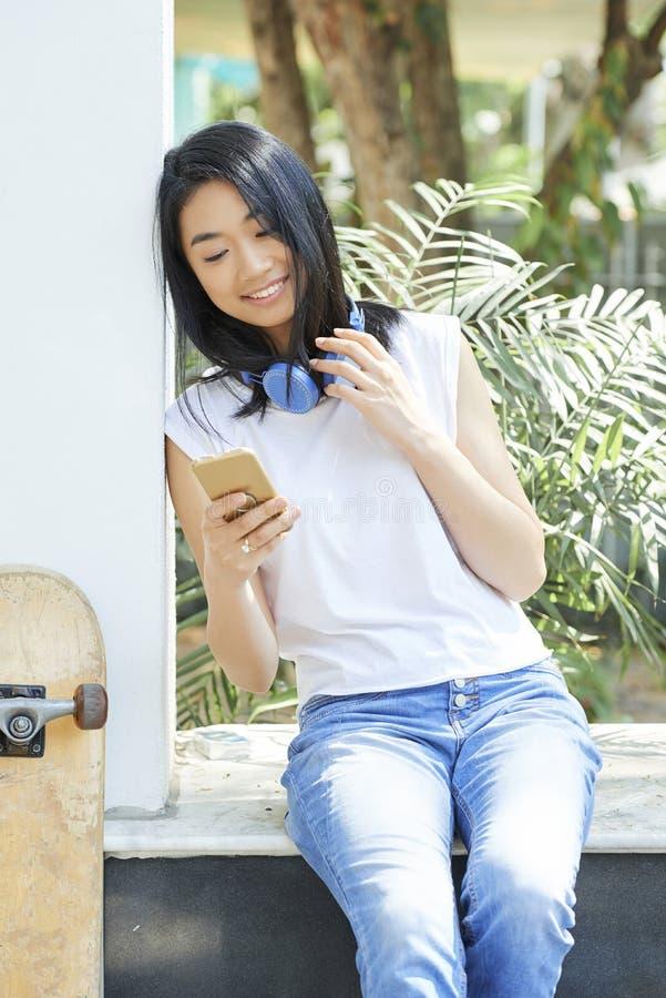 Tonårs- flicka som kontrollerar smartphonen fotografering för bildbyråer