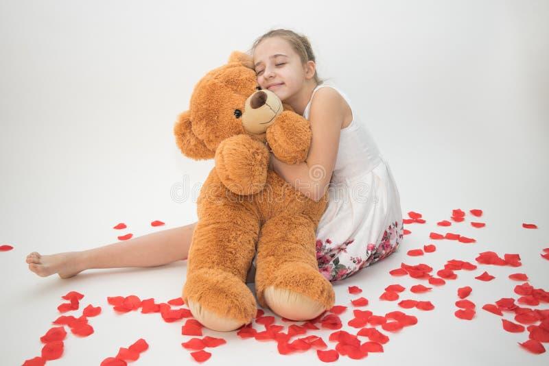 Tonårs- flicka som kramar en nallebjörn arkivfoton