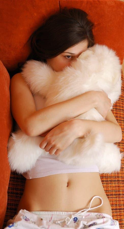 Tonårs- flicka som kramar med en kelig leksak i soffasängen royaltyfri fotografi