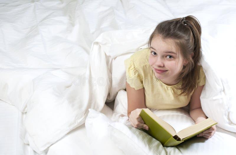 Tonårs- flicka som läser en bok i säng arkivbild