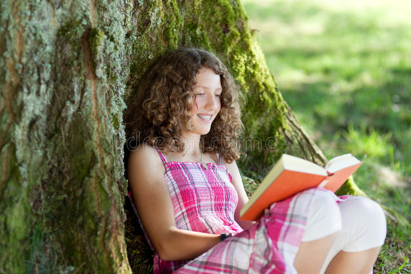 Tonårs- flicka som läser en bok under ett träd royaltyfria bilder